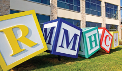 giant child-style play blocks spelling R M H C and rmhc logo
