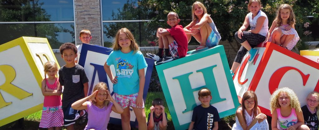 """group of children gathered in front of large child-like blocks spelling """"RMHC"""""""