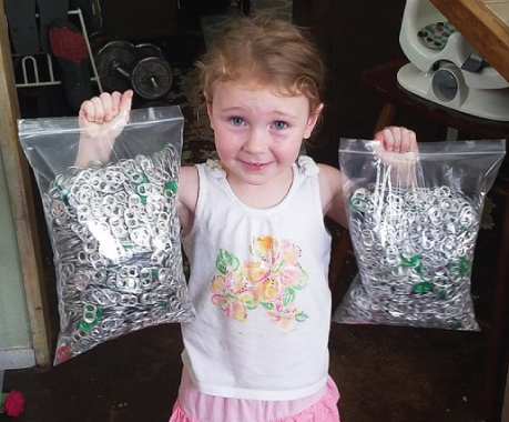 young girl holding two large bags full of collected pop tabs for donation