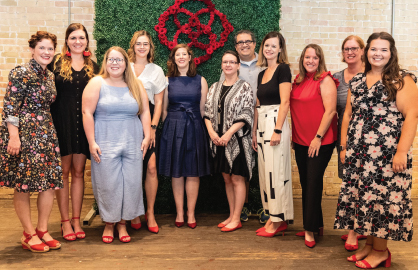 red shoe society members all with red dress shoes on smiling and gathered for fundraising event