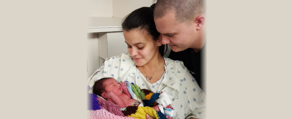 Sarah smith and her husband holding their newborn daughter