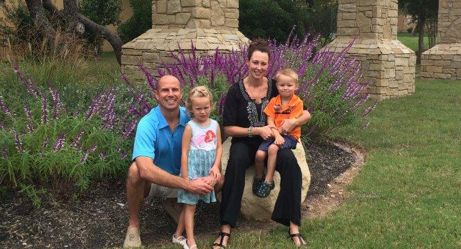 Chris Szeliga, Vice President of JE Dunn Construction in Austin and his family smiling outside next to a garden