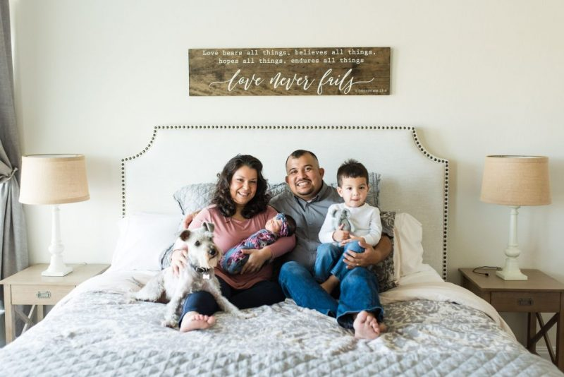 Monica Velez and her husband Erik their two children and dog sitting on bed and smiling
